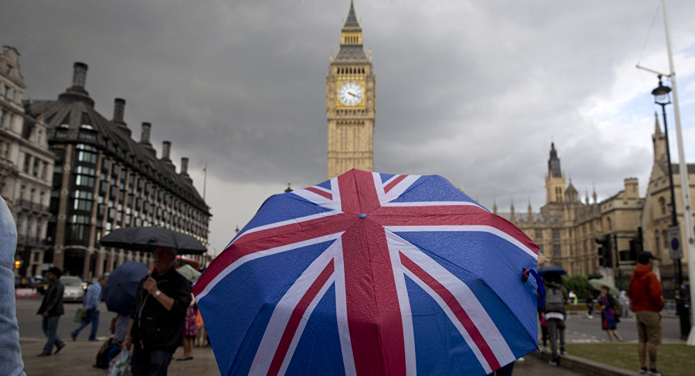 A pedestrian shelters from the rain beneath a Union flag themed umbrella as they walk near the Big Ben clock face and the Elizabeth Tower at the Houses of Parliament in central London on June 25, 2016.