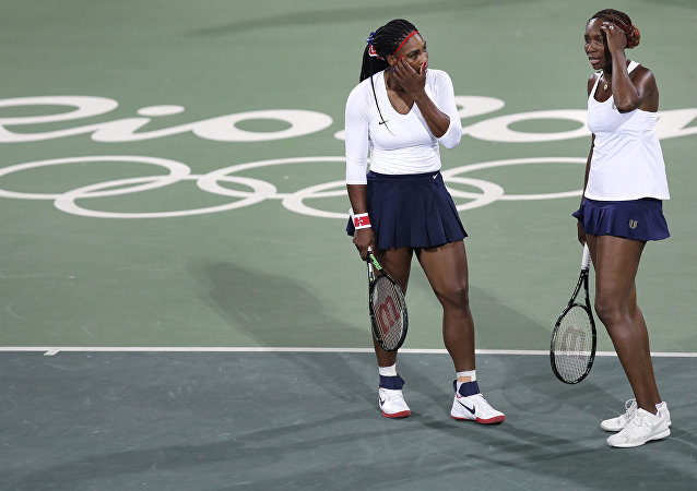 Venus Williams, of the United States, right, talks with her sister Serena after losing a point in a doubles match against Lucie Safarova and Barbora Strycova, of the Czech Republic, at the 2016 Summer Olympics in Rio de Janeiro, Brazil