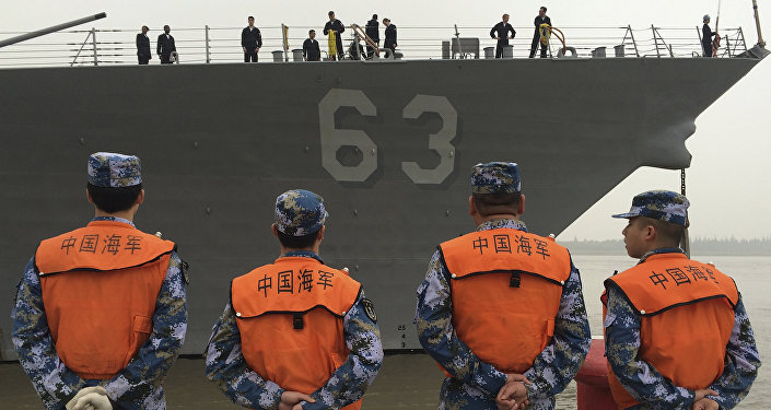 Chinese Navy personnel stand watch the guided missile destroyer USS Stethem arrives at the Shanghai International Passenger Quay for a scheduled port visit in Shanghai, China, Monday, Nov. 16, 2015.