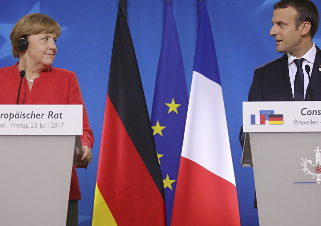 German Chancellor Angela Merkel, left, and French President Emmanuel Macron prepare to address the media at an EU summit in Brussels on Friday, June 23, 2017.