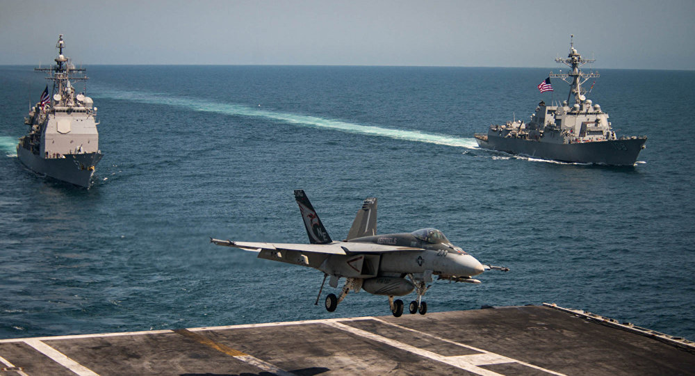 An F/A-18E Super Hornet lands on the flight deck of the U.S. Navy aircraft carrier USS Carl Vinson as the Ticonderoga-class guided-missile cruiser USS Lake Champlain (L) and the Arleigh Burke-class guided-missile destroyer USS Wayne E. Meyer transit the western Pacific Ocean May 3, 2017.