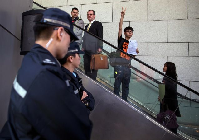 Hong Kong student leader Joshua Wong, 18, gestures to supporters as he arrives at the police headquarters in Hong Kong January 16, 2015