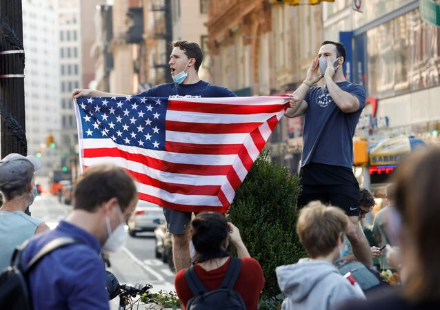 A man holds U.S. flag as people celebrate media announcing that Democratic U.S. presidential nominee Joe Biden has won the 2020 U.S. presidential election on Union Square in the Manhattan borough of New York City, U.S.