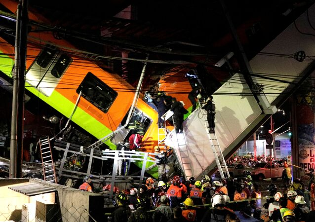 Rescuers work at a site where an overpass for a metro partially collapsed with train cars on it at Olivos station in Mexico City, Mexico May 03, 2021.