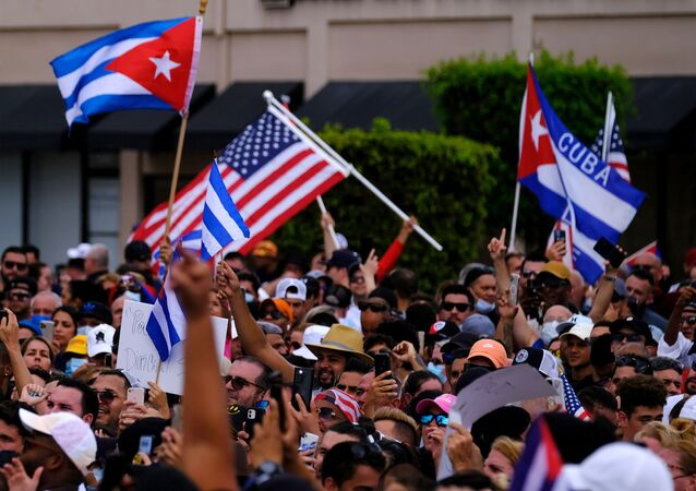 Emigres in Little Havana wave American and Cuban flags as they react to reports of protests in Cuba against the deteriorating economy, in Miami, Florida, U.S., July 11, 2021
