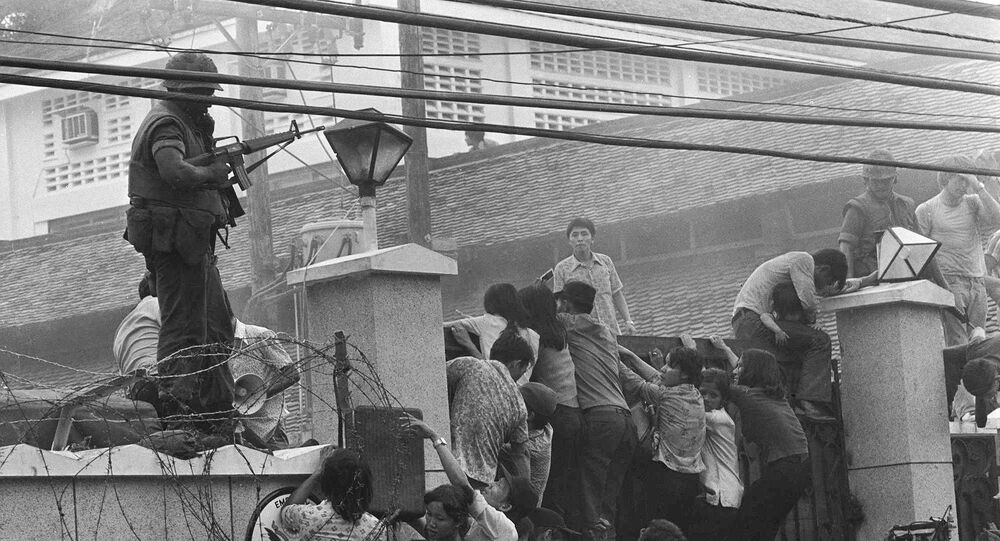 People clamber into the US embassy compound during the fall of Saigon in 1975
