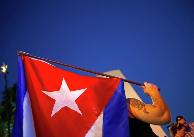 An anti-Castro Cuban exile holds a Cuban flag during a protest after the announcement of restoring diplomatic ties between Cuba and United States, at an area knows as 'Little Havana' in downtown Miami, Florida December 17, 2014.