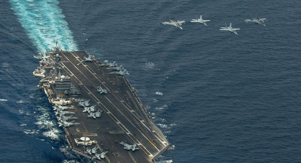 Two F/A-18 Super Hornets and two Royal Malaysian Air Force Mig 29 Fulcrum fly in formation above aircraft carrier USS Carl Vinson