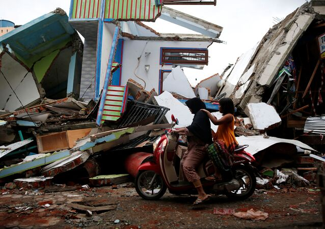 A woman and child ride a motorcycle past damaged buildings following this week's strong earthquake in Meureudu market, Pidie Jaya, Aceh province, Indonesia December 9, 2016.