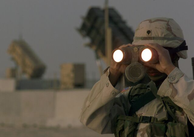 US soldier uses a pair of binoculars to scans the landscape around his Patriot Missiles based at Al Udeid AB, Qatar
