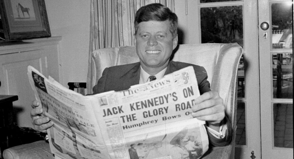 Sen. John F. Kennedy (D-MA) reads the daily newspaper accounts of his West Virginia election victory as he relaxes, May 11, 1960, in his Washington home. Kennedy defeated Sen. Hubert Humphrey (D-MN) in yesterday's presidential primary.