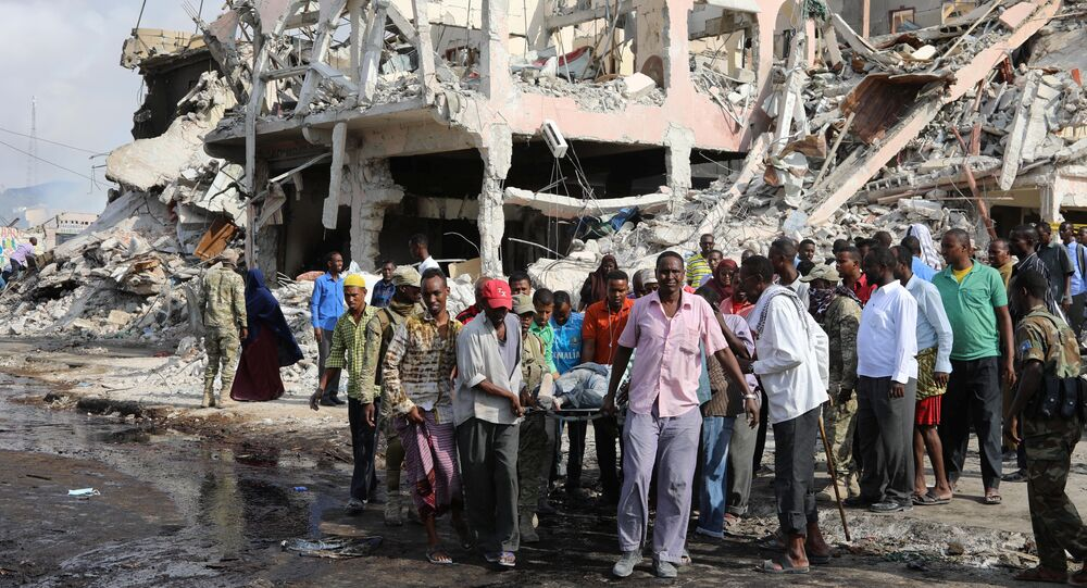 Civilians carry the body of an unidentified man from the scene of an explosion in KM4 street in the Hodan district of Mogadishu, Somalia October 15, 2017