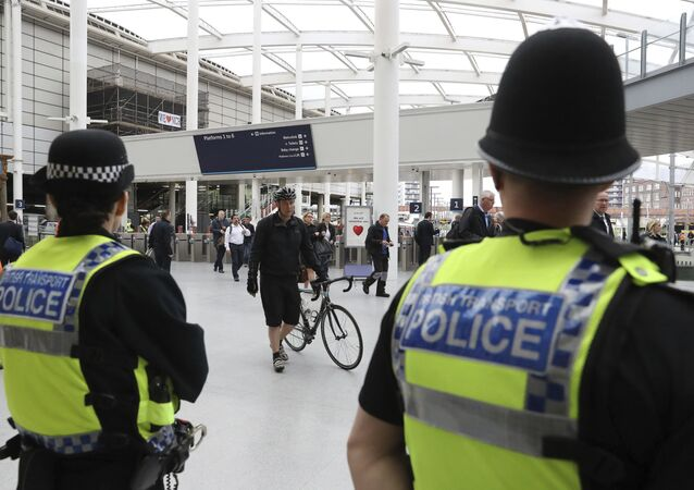 Police watch as commuters pass through Manchester Victoria railway station in Manchester England, which has reopened for the first time since the terror attack on the adjacent Manchester Arena Tuesday May 30, 2017