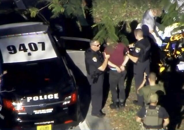 A man placed in handcuffs is led by police near Marjory Stoneman Douglas High School following a shooting incident in Parkland, Florida, U.S. February 14, 2018 in a still image from video