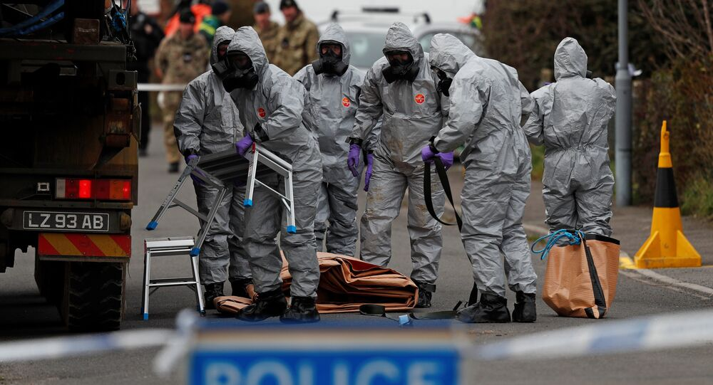 British Military personnel wearing protective coveralls work to remove a vehicle connected to the March 4 nerve agent attack in Salisbury, from a residential street in Gillingham, southeast England on March 14, 2018