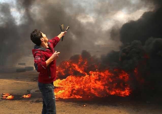 A Palestinian man uses a slingshot during clashes with Israeli forces along the border with the Gaza strip east of Khan Yunis on May 14, 2018, as Palestinians protest over the inauguration of the US embassy following its controversial move to Jerusalem