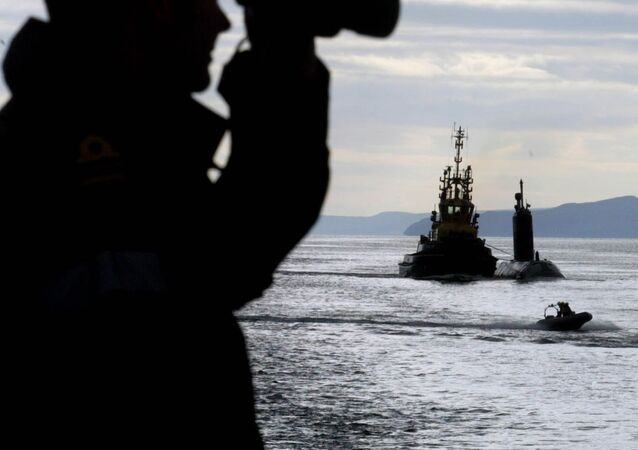 British Royal Naval Officer Paul Matthews, left, onboard the British frigate HMS Montrose watches as a tug boat tows the Canadian submarine HMCS Chicountimi up the River Clyde towards the British Naval Base at Faslane, Scotland.