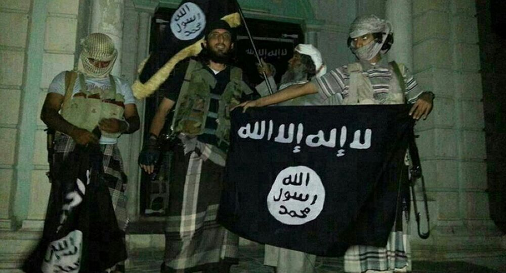A picture taken with a mobile phone early on May 24, 2014 shows Al-Qaeda militants posing with Al-Qaeda flags in front of a museum in Seiyun, second Yemeni city of Hadramawt province, after launching a massive pre-dawn assault that killed at least 15 soldiers and police