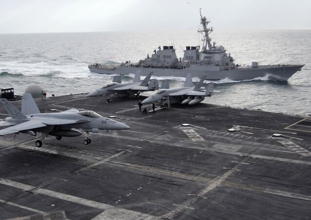 This file photo taken on Monday, Feb. 13, 2012 shows a U.S. F-18 fighter jet, left, land on the Nimitz-class aircraft carrier USS Abraham Lincoln (CVN 72) as a U.S. destroyer sells on alongside during fly exercises in the Persian Gulf
