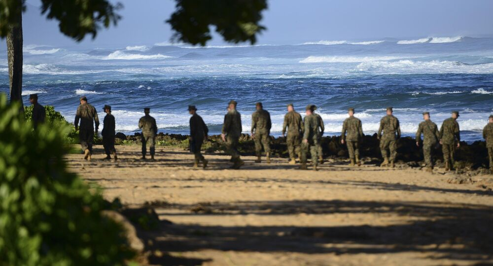 A group of Marines walk the beach outside the Haleiwa Incident Command Post in Haleiwa, Hawaii, during search efforts for 12 missing Marines, in this handout photo taken January 18, 2016