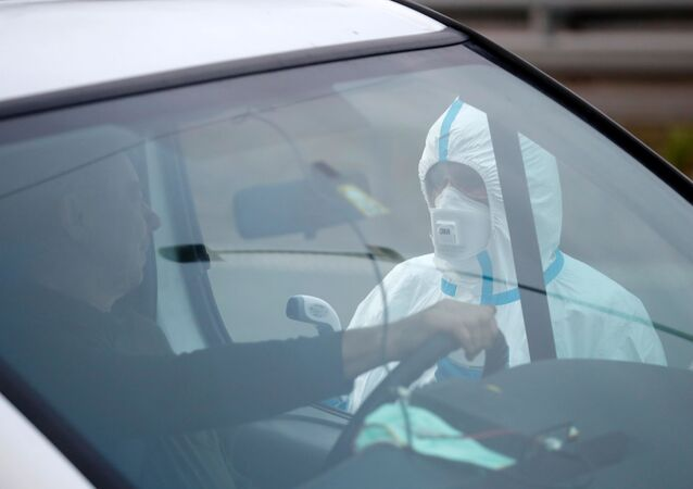 A picture taken on March 9, 2020 on the Polish side shows a medical staff taking the temperature of a driver during sanitary checks at Jedrzychowice border crossing, between Poland and Germany, in a measure to protect against the spread of the novel coronavirus.
